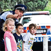 Police officer standing with children at road side.