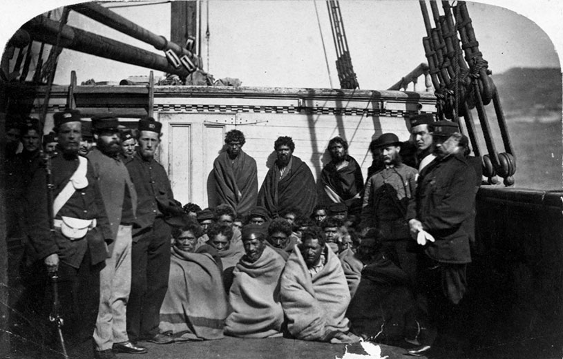Māori prisoners who were members of the Hauhau church, under guard on board a prison hulk in Wellington harbour, 1866. Alexander Turnbull Library (1/2-103605F)