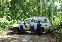 New Zealand Police Superintendent Murray Lewis and two Bougainville Police service officers by a vehicle across forest road near Buin, southern Bougainville.