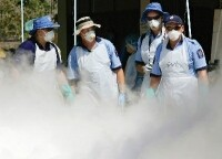 Four New Zealand Police officers surrounded by a sterilising mist at Wat Yan Yao mortuary, Phuket, Thailand.