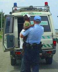 New Zealand Police officer Clayton Sargisson carrying a five-year old boy to an ambulance in Dili, Timor-Leste. The boy had been in a motor accident.