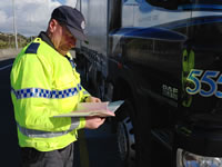 Photo of an officer checking truck documents by the road