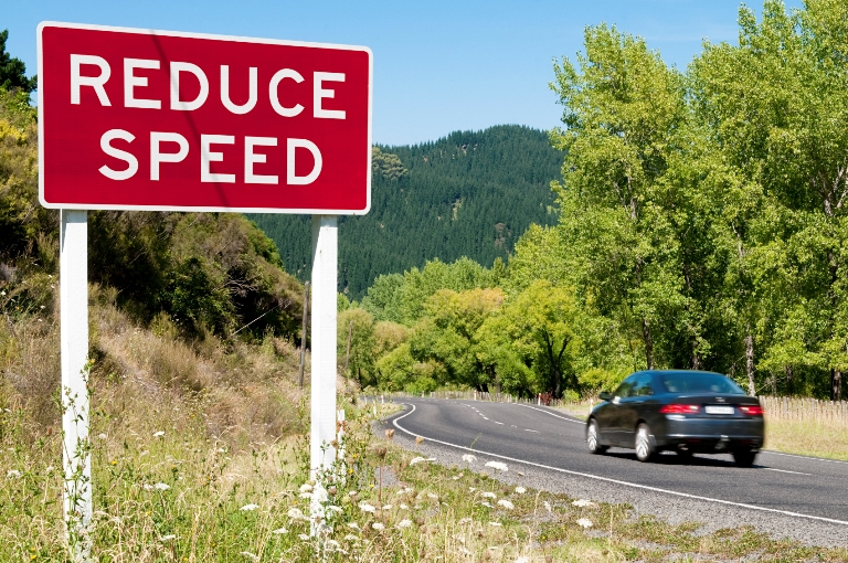 A car drives past a reduce speed sign on the open road.