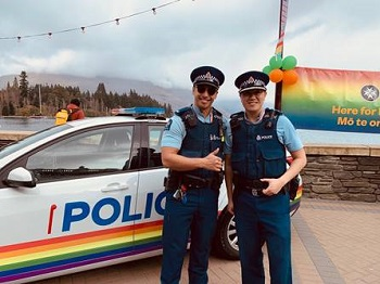 police car with rainbow printed on it and two men officers standing in front