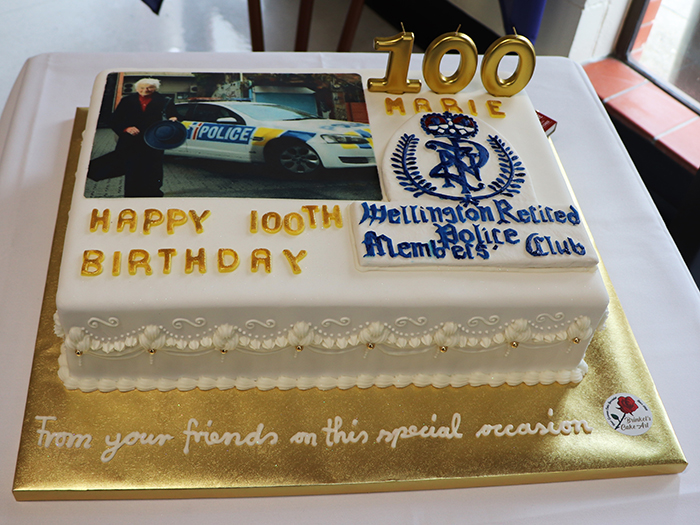 A birthday cake from the Wellington Retired Police Members' Club featuring a photo of Marie and the New Zealand Police crest.