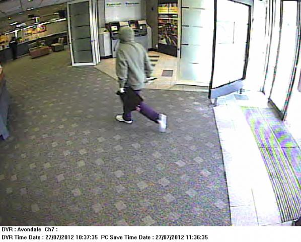 Security camera picture of a man in a green hoodie entering a bank.