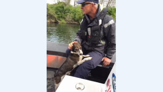 Sergeant Craig Kennedy and the dog rescued from the Waikato River
