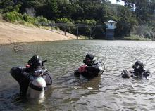 Police National Dive Squad members preparing for a search of the Ross Creek Reservoir in April 2014
