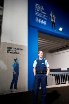 Sergeant Dee Teao standing in front of painted street art image of herself on wall