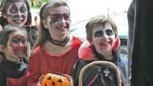 Kids dressed in Halloween costumes standing at doorway.