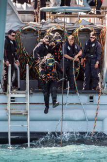 Navy divers from the Royal New Zealand Navy Operational Dive Team enter the water at the site of the sunken FV Jubilee