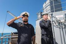 Members of the diving support vessel HMNZS MANAWANUI performing a 'Piping of the Side' as a mark of respect