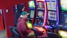 two men siting at pokies one in red hoodie green cap and another in black hoodie, related to case 3 of episode 33