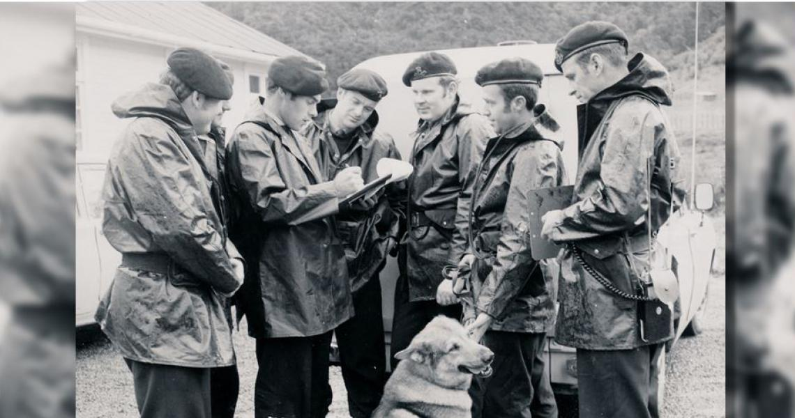 AOS Commander Bernie, with clipboard, briefs staff including Tom Penrose, seen second from right with his dog Ochre.
