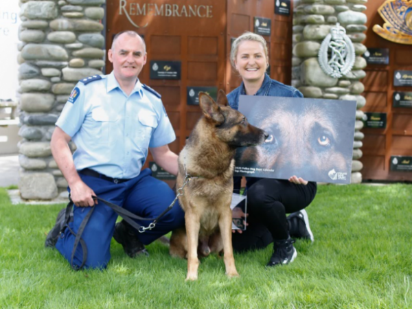 Police dog Arlo gives his seal of approval as Inspector Todd Southall presents Constable Jane Dunn her award