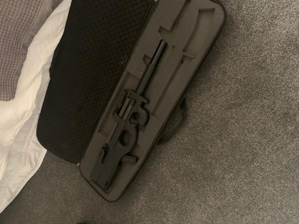 A prohibited firearm in a black case which was recovered during a search warrant.