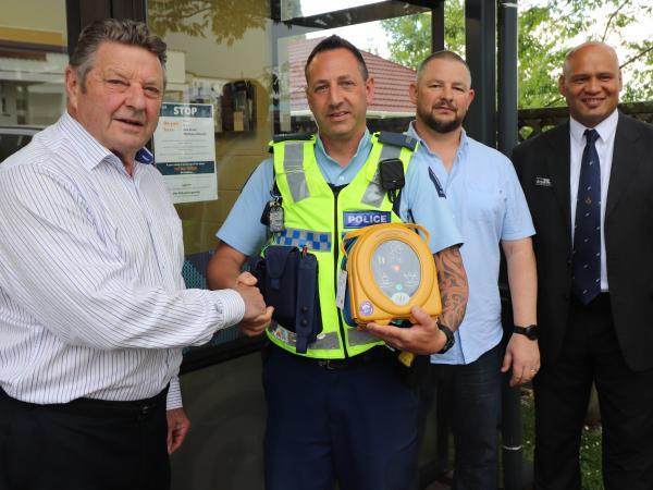 Whitianga Freemasons Master Elect John Smart presents the defibrillator to Constable Nick Preston, alongside Freemasons Marc Dre