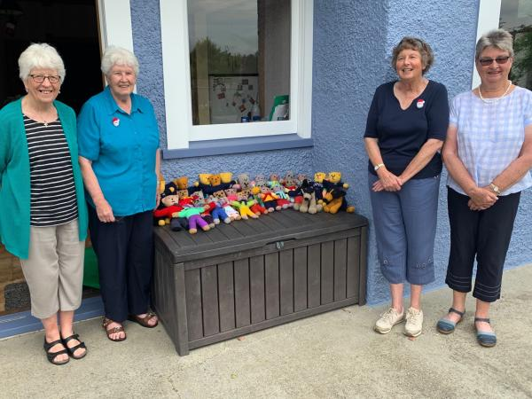 Pam (wearing the navy top) and some members of her knitting circle with their bevy of care bears.
