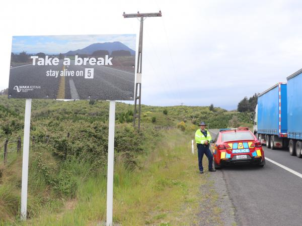 Constable Steven Knox beside one of the new 'Stay Alive on 5' signs.