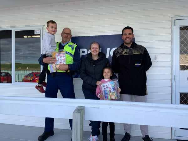 Group shot with John holding up Marie O'Brien's son next to Marie, her daughter and her husband, outside the Ohakea Patrol Base.