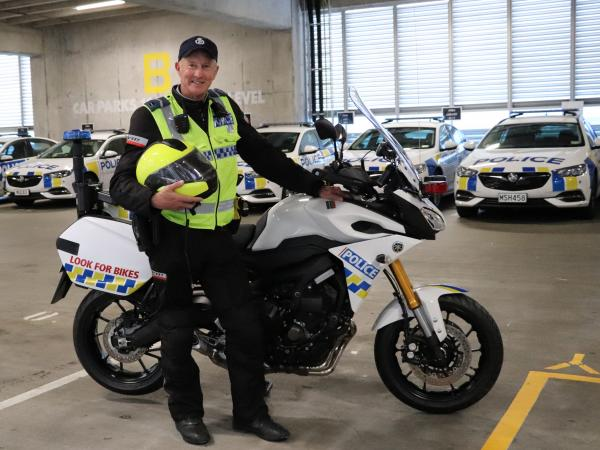 Senior Constable Johnny McGrail, in uniform, standing in front of a Police motorbike in a garage with police cars behind him.