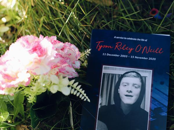 Flowers next to an order of service with Tyson's photo on the cover.