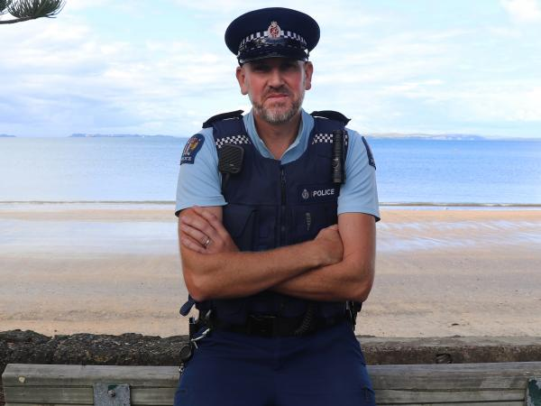 Constable Rob Gormly resting on the back of a bench with the waterfront behind him.
