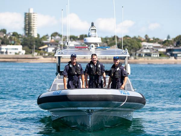 Three Wellington Maritime Unit staff standing at the back of a police launch in the middle of Auckland harbour.