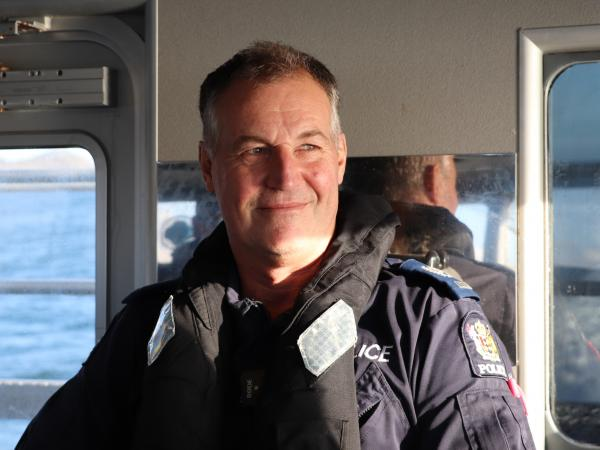 Profile picture of retired Senior Sergeant Tex Houston sitting in the Lady Liz with reflecting the afternoon sunshine.