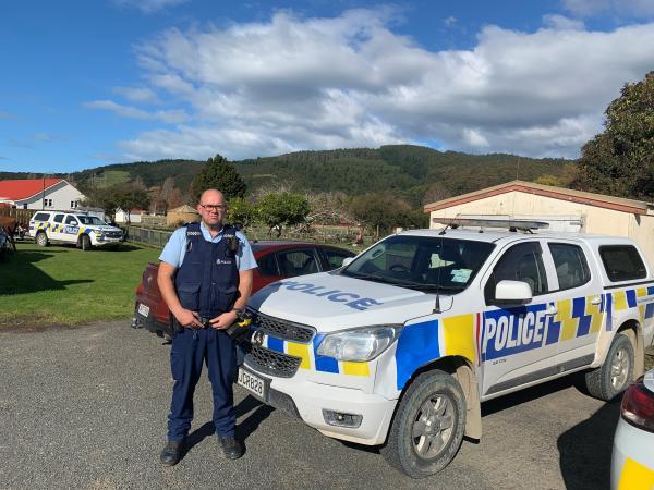 Justin in uniform next to a police car in Ruatoria