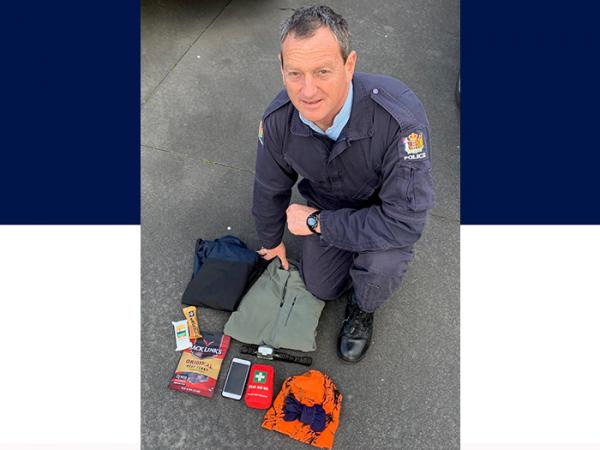 Senior Constable Peter Karam with some essentials for a bush trip, including a raincoat, fleece, food & fully charged cellphone.