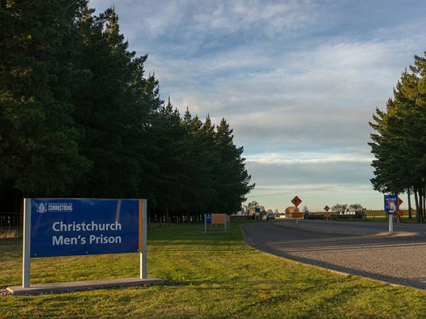 A sign saying Christchurch Men's Prison at the entrance of the driveway to the prison.