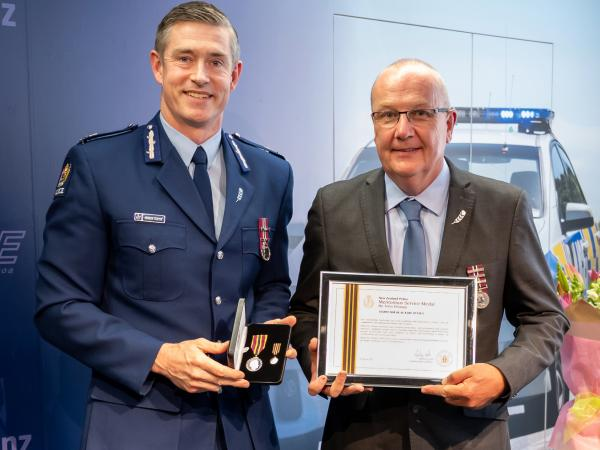 Commissioner Andrew Coster presents Olaf Jensen with his MSM.