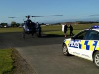 Police dog 'Gus' being carried to the helicopter that took him to Auckland