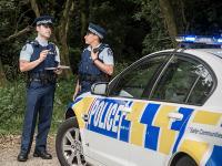 Police staff by car in bush location