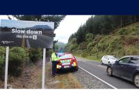 Senior Constable Steven Knox next to a road safety sign on the Napier-Taupo Road